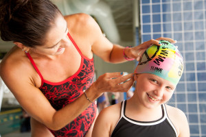 Kristy Kowal helps Carly with her cap as they prepare for the swim